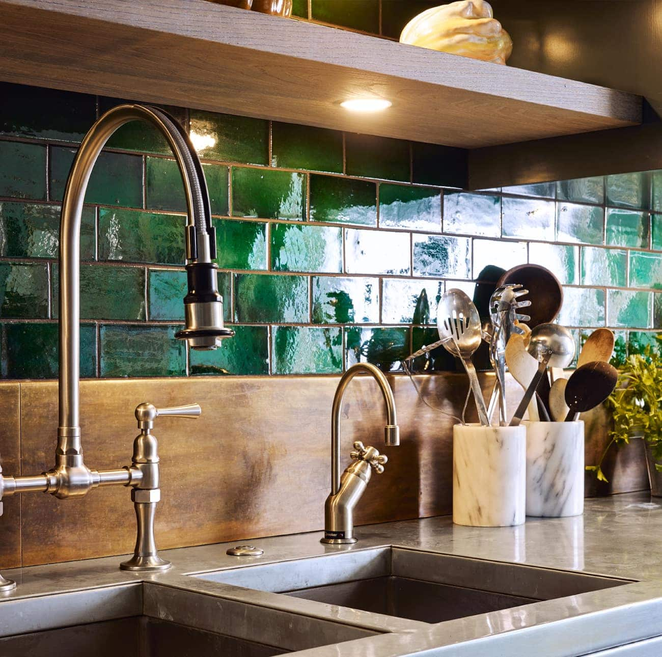 Industrial taps with green wall tiles and wooden splashback