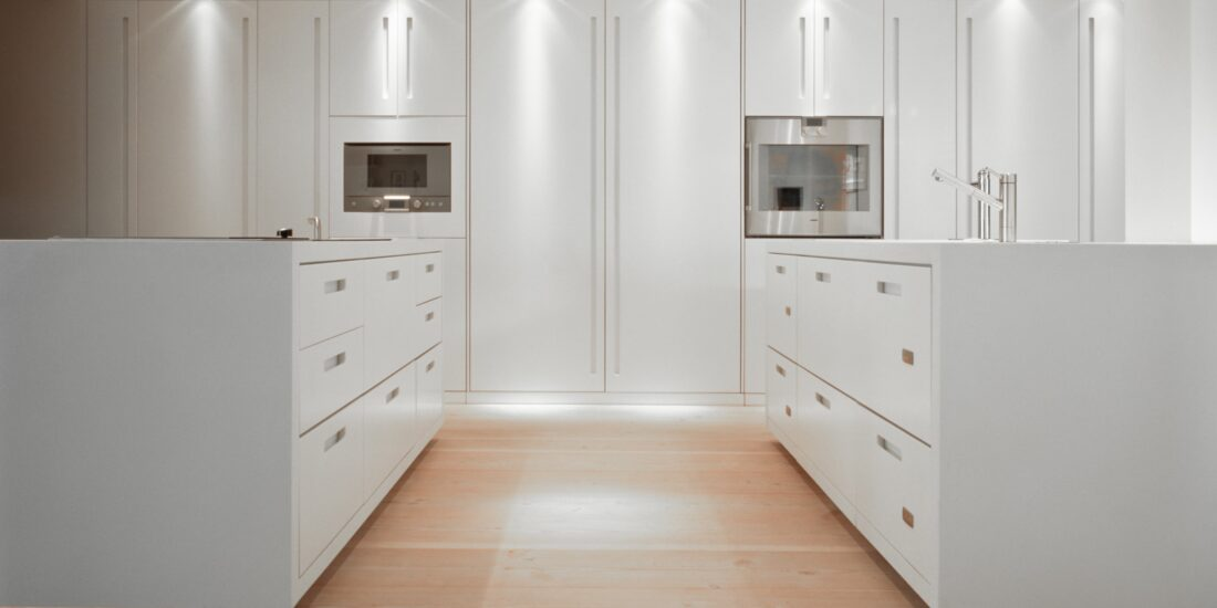 Modern white kitchen featuring raised built-in microwave and oven in white cabinets with inset handles.