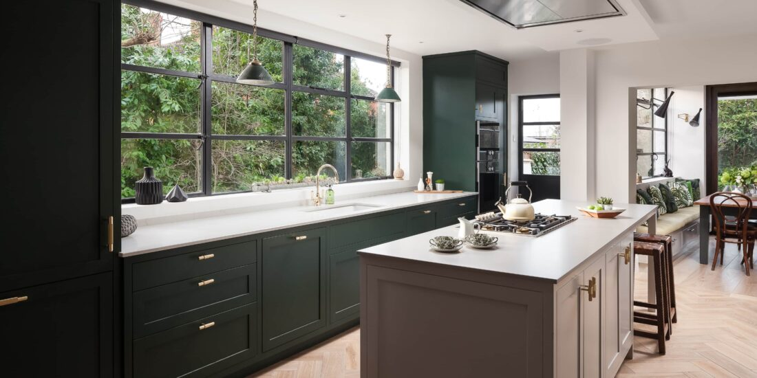 Modern green and beige kitchen cabinets, with parquet wooden floor and white work tops.