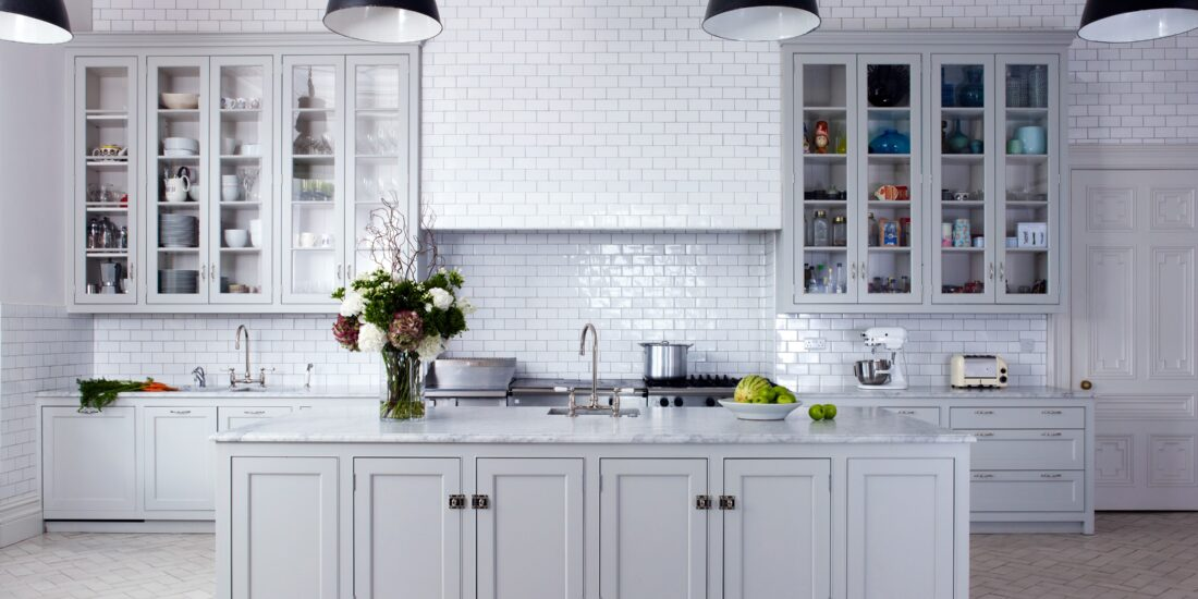 Classic kitchen with solid and glass fronted white cabinets, white wall tiles and black industrial lights.