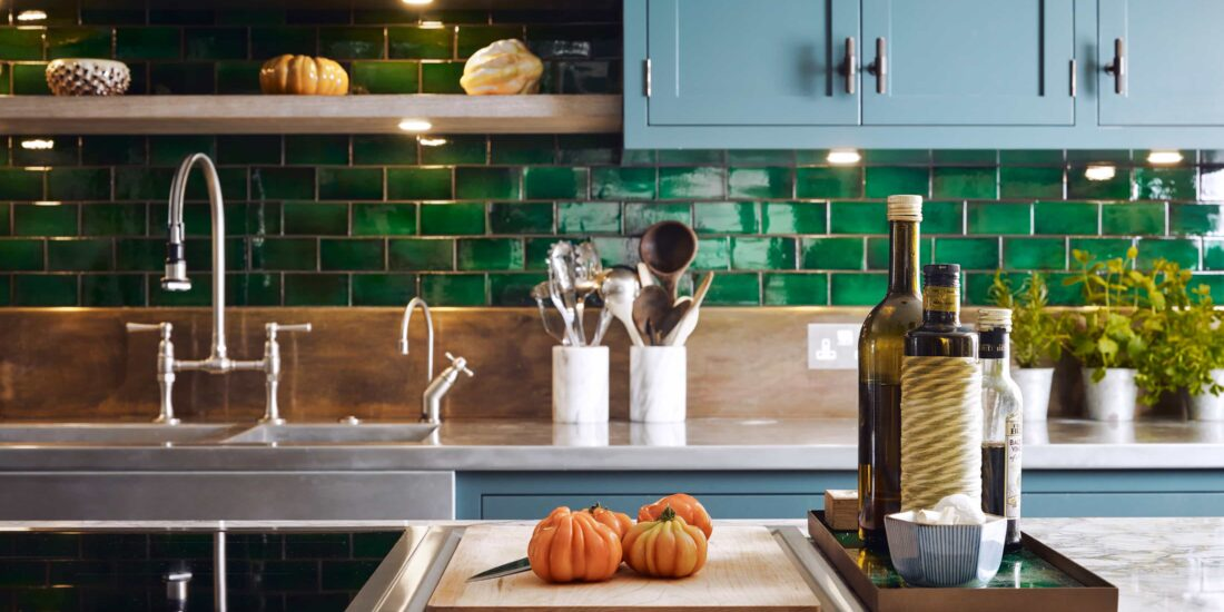 Kitchen with green titles, wooden splashback board, and industrial style cabinets and taps. marble effect worktops