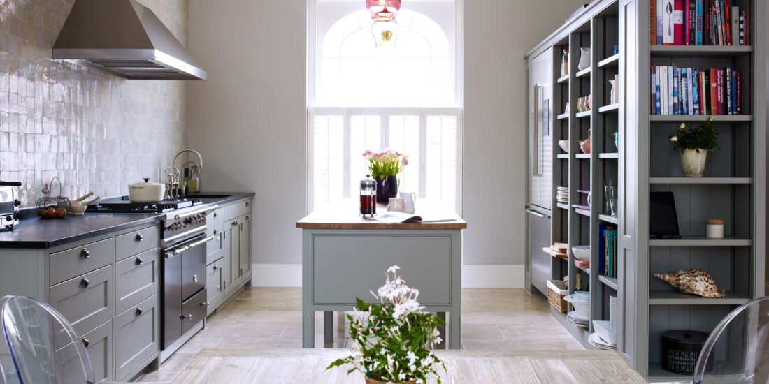 The heritage kitchen range with classic grey cabinets, aga oven, island and bookshelves with built-in fridge.
