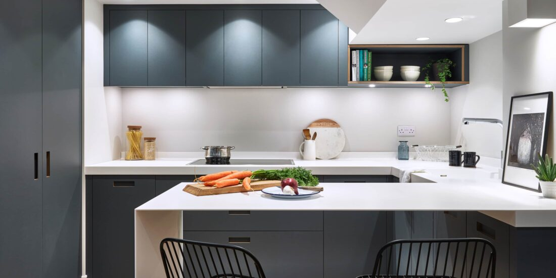 Modern dark grey kitchen cabinets with inset handles, paired with white work tops, spot lights and industrial wire chairs.
