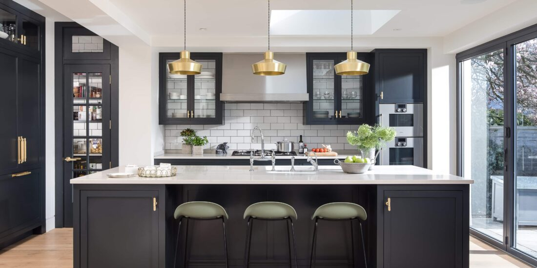 Dark cabinet fronts with white work surfaces, glass windowed pantry cupboard, raised ovens and brass industrial lighting.