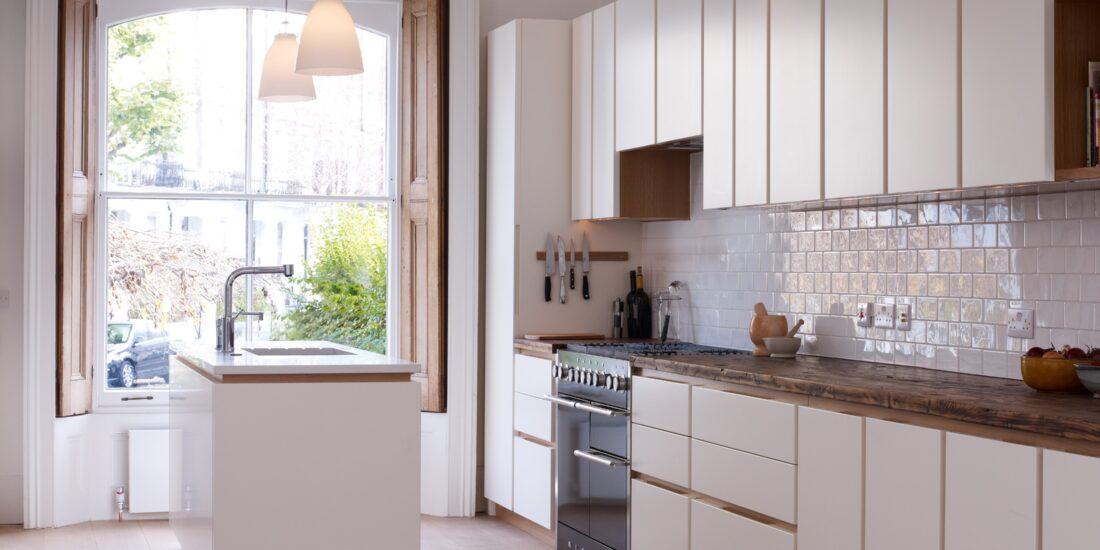 White unit fronts with wood work surfaces, cabinet interiors, flooring and skirting boards.