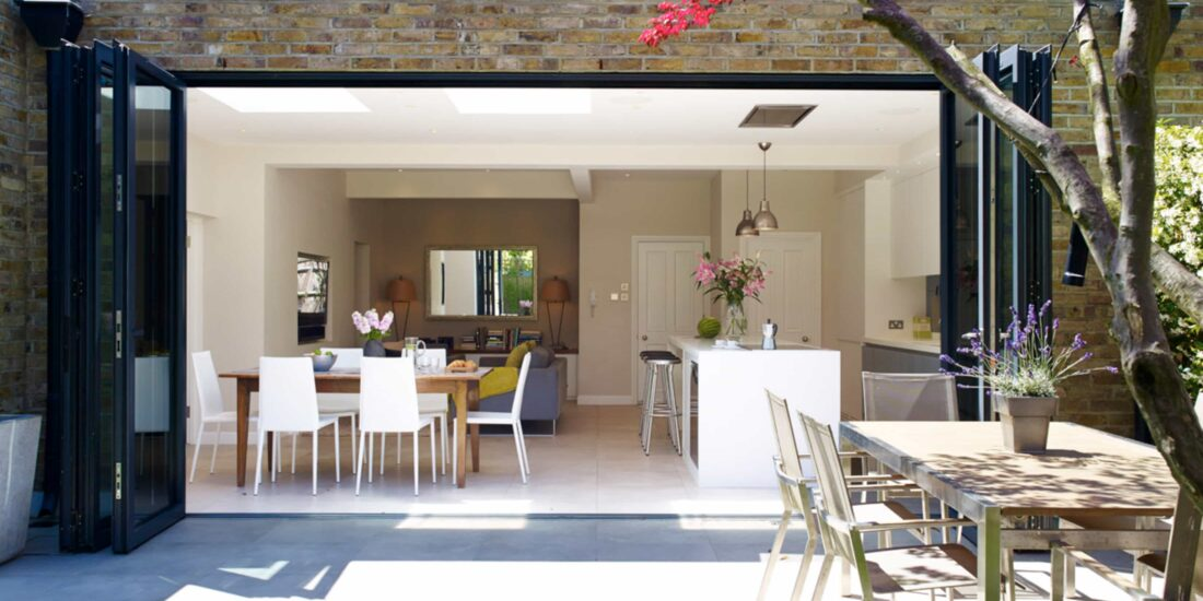 The open-plan kitcen extension has large by-folding doors, as well as classic white cabinet fronts and dining space.