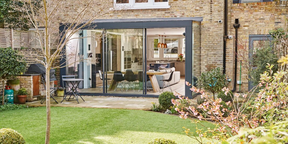 The exterior of the kitchen extension has grey metal work and three large sliding glass doors.