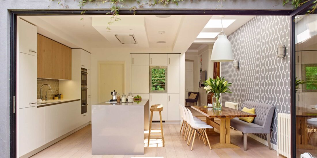 Open-plan kitchen diner extension with white cabinet fronts, paired with wood features and whole side by-fold doors.