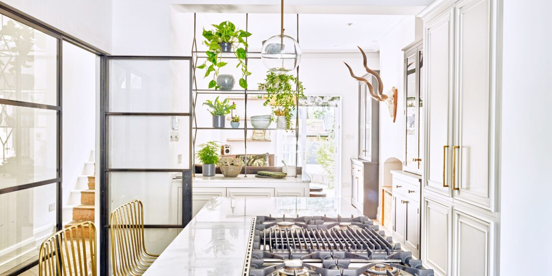 Traditional kitchen diner with a modern twist, featuring an island with gas hob and glass doors to the hall.