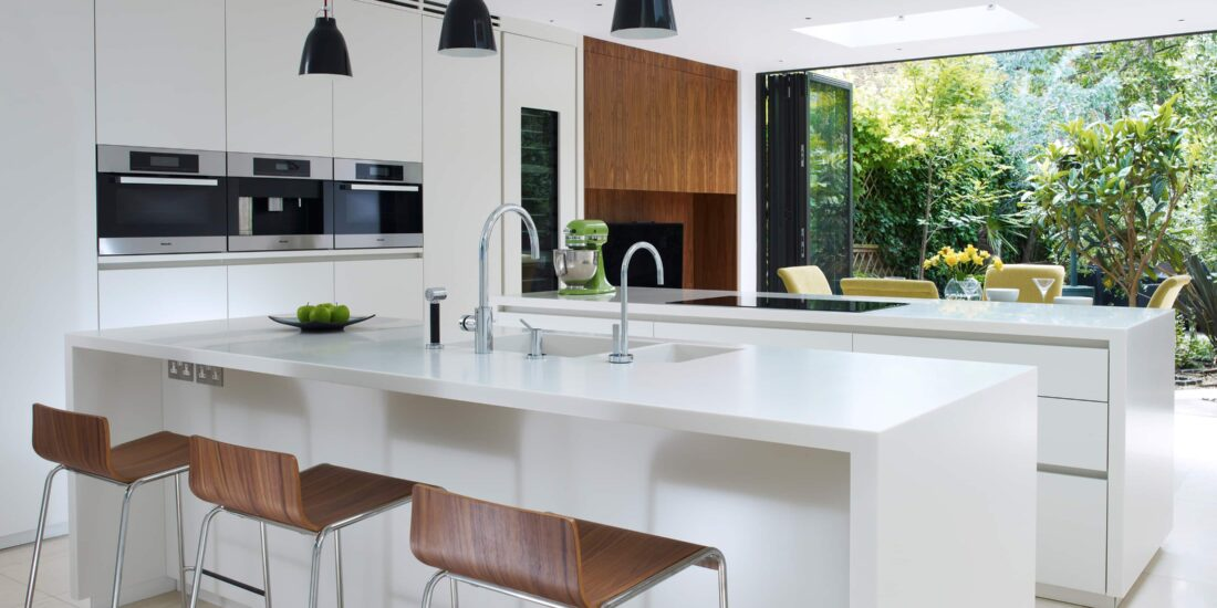 Classic white kitchen cabinets and islands with three oven, wood affect features, by-fold doors and industrial lighting.