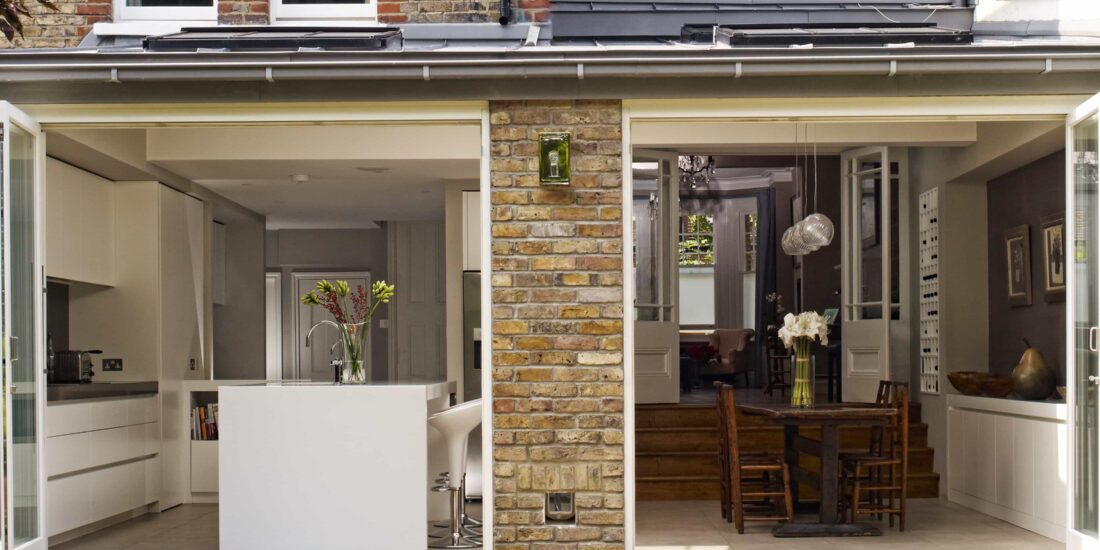 Side view of a kitchen diner extension that has two sets of by-fold doors with a central divide.