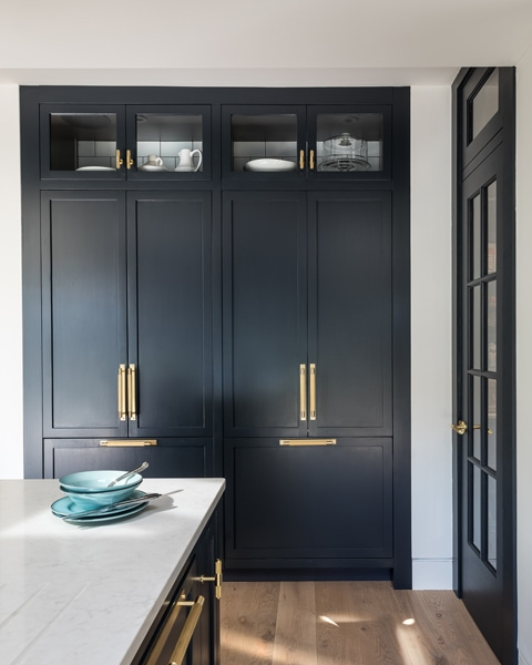 Stylish Lowther kitchen cabinets with brass handled and glass fronted panels at the top