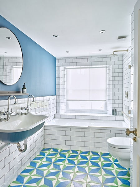 Blue themed bathroom with white wall tiles and green, blue and white floor tiles.