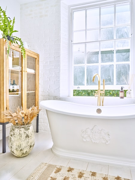 Myddleton style bathroom with standing bath, large glass cabinet and brass tap.