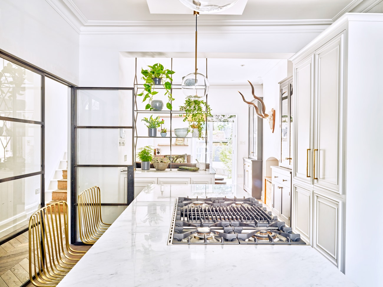Marble work top with built-in gas hob and brass coloured wire seating