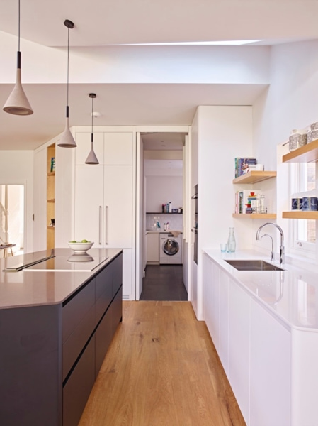 Modern kitchen with white units to the right and dark to the left, with a view through to the utility room.