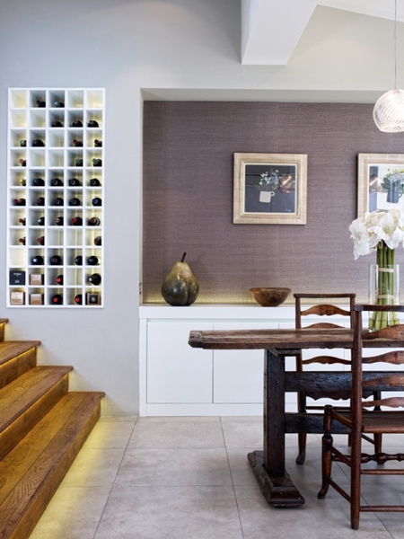 Wooden staircase with wine rack in the wall leading into a modern dining room with an antique dining table.