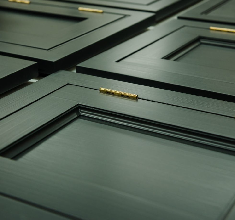Khaki green cabinet example fronts with brass hinges.