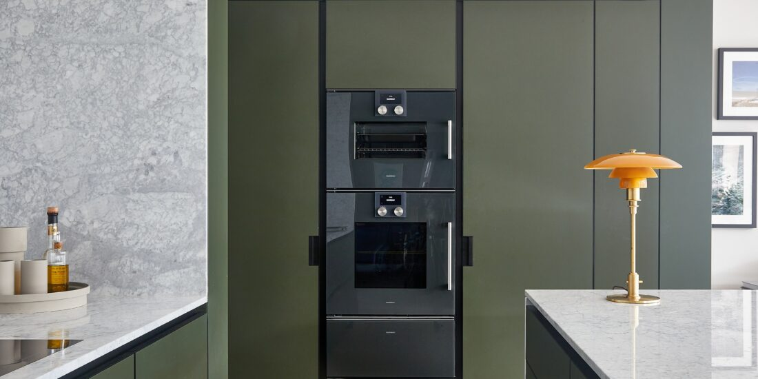 Fitted raised ovens and proving drawer, within a khaki green build-in cabinet set with marble effect work tops to the side.
